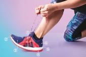 Woman lacing up running shoe