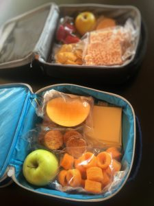 Two packed lunches in lunchboxes. Including fruit and processed foods.