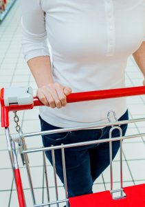 Asian woman pulling a shopping cart in a supermarket.
